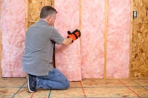A homeowner installing fiberglass insulation as part of Penticton, B.C.'s energy retrofit program.